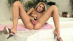 Hor blonde with big tits and round ass uses a big pink dildo to show her curves