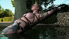 Inked up blonde chick gets tied up and dipped in the cool water