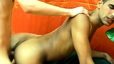 The brunette stud bends over and his lover fucks his ass bareback from behind